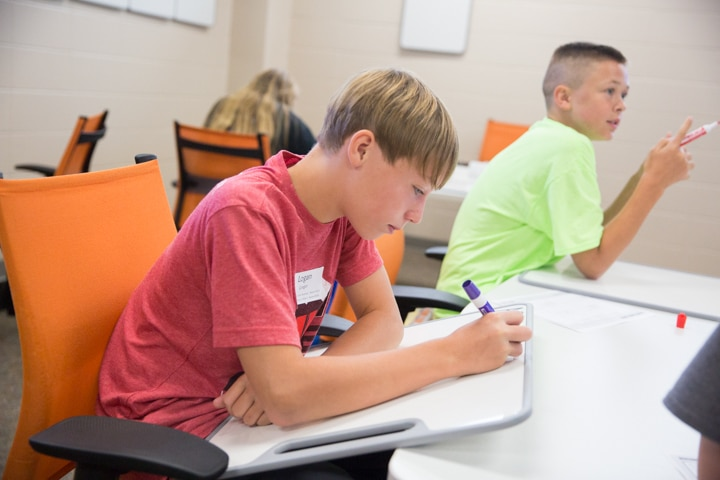 Boy uses marker on whiteboard at TKC