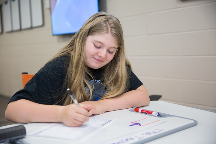Girl smiles while working on project at Moraine Park Tech Knowledge College