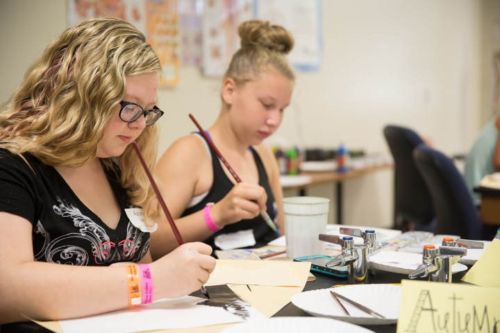 Two girls work on painting projects at Moraine Park TKC