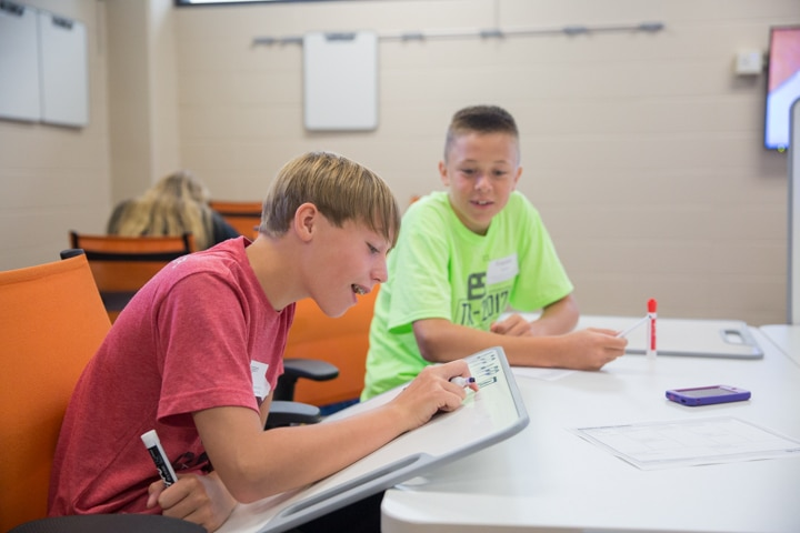 Boys work with whiteboards during TKC business session
