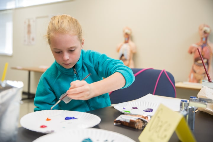 Girl works on painting project at Moraine Park Tech Knowledge College