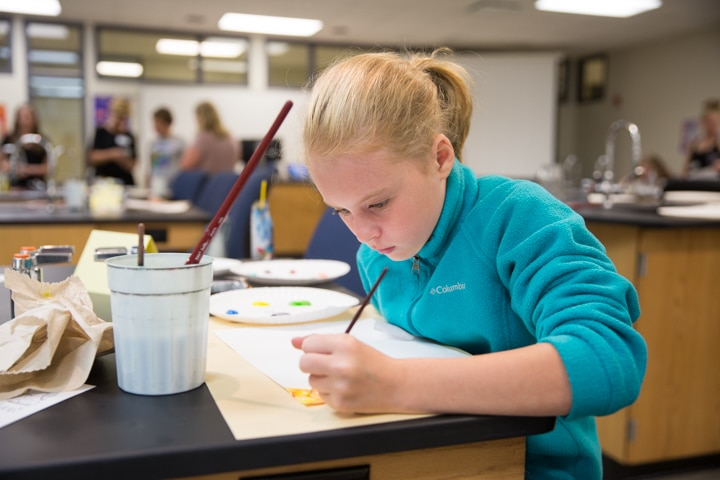 Girl works on painting project at Moraine Park TKC summer camp