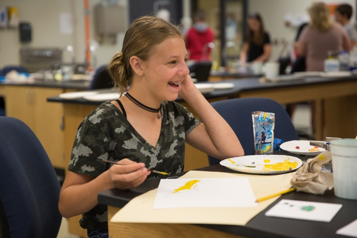 Girl laughs while doing painting project at Moraine Park Tech Knowledge College