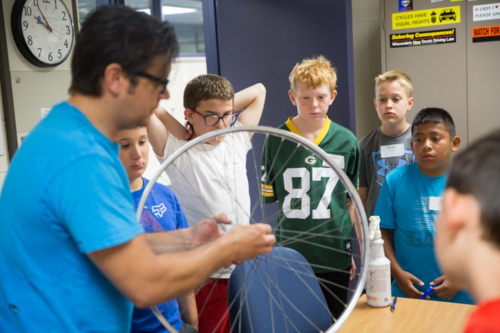 Students listen to instructor during bike wheel demonstration