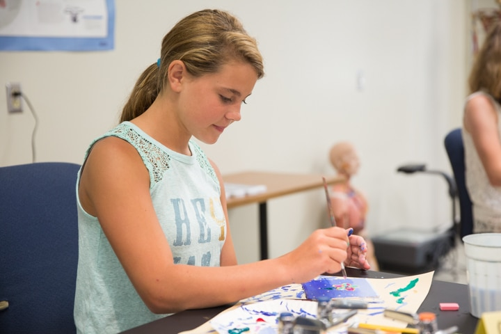 Girl works on painting project during Moraine Park TKC summer camp