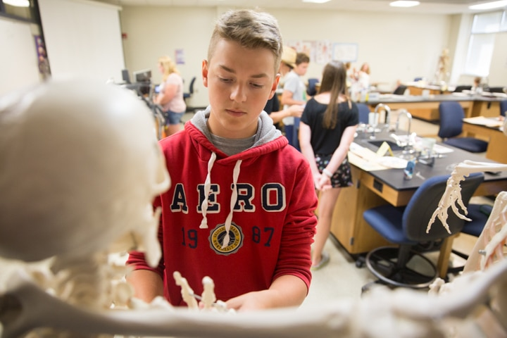 Boy plays with classroom skeleton during art class at Moraine Park TKC