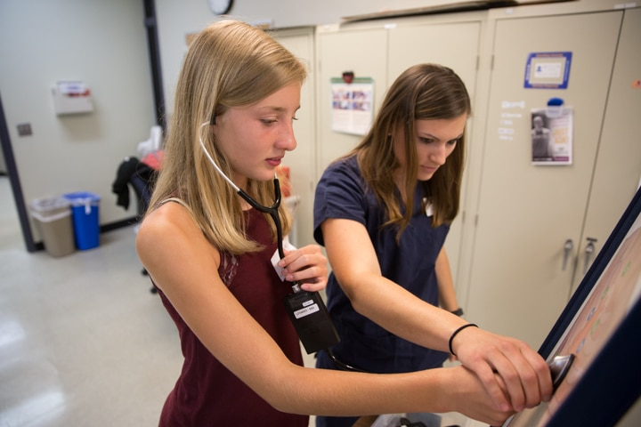 Instructor helps girl use stethoscope to hear simulated chest sounds at Moraine Park Tech Knowledge College