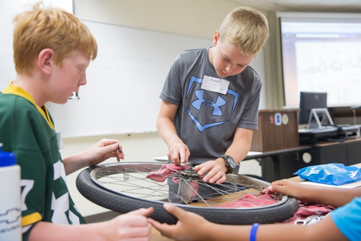 Boys tighten bike tire parts with wrench at Moraine Park Tech Knowledge College
