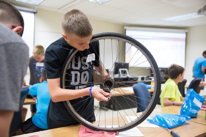 Boy inserts part into center of bike wheel at Moraine Park Tech Knowledge College