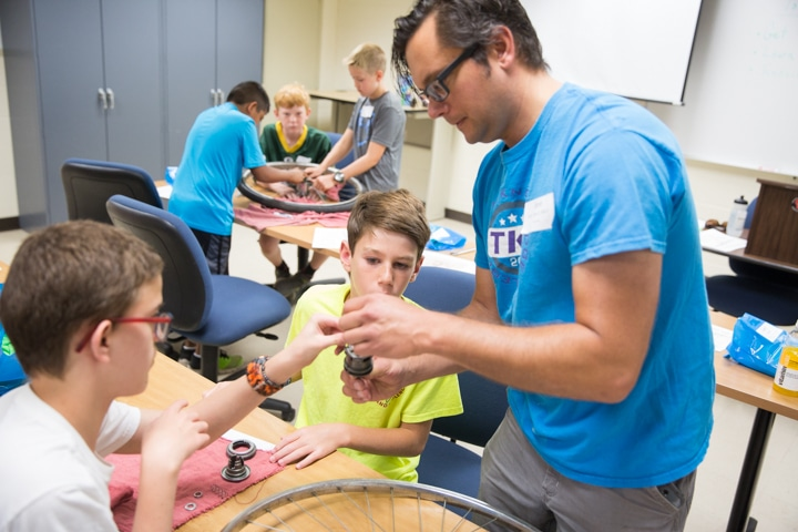 Instructor helps two boys with bike tire part assembly during TKC activity at Moraine Park