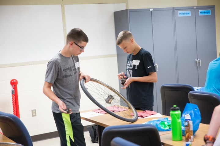Two boys work on bike tire at Moraine Park TKC summer camp