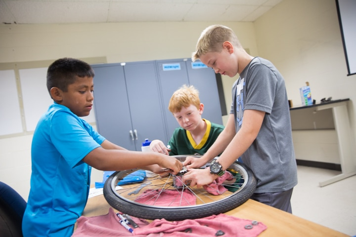 Three boys assemble bike tire during Moraine Park Tech Knowledge College in Fond du Lac