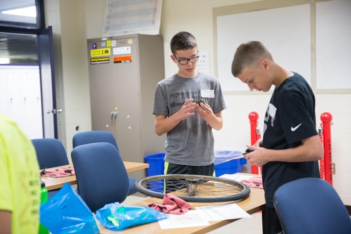 Boys inspect bike tire parts at Moraine Park Tech Knowledge College