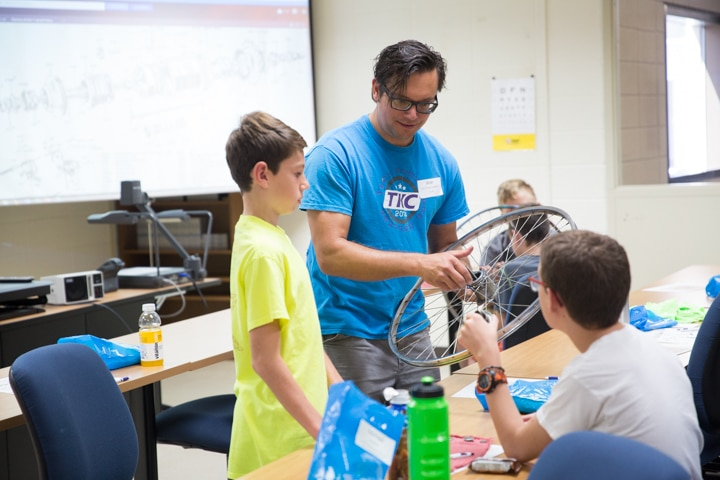 Instructor helps students assemble bike tire parts at Moraine Park TKC summer camp