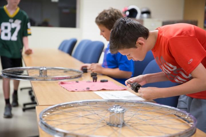 Boys assemble bike tires during Moraine Park Tech Knowledge College