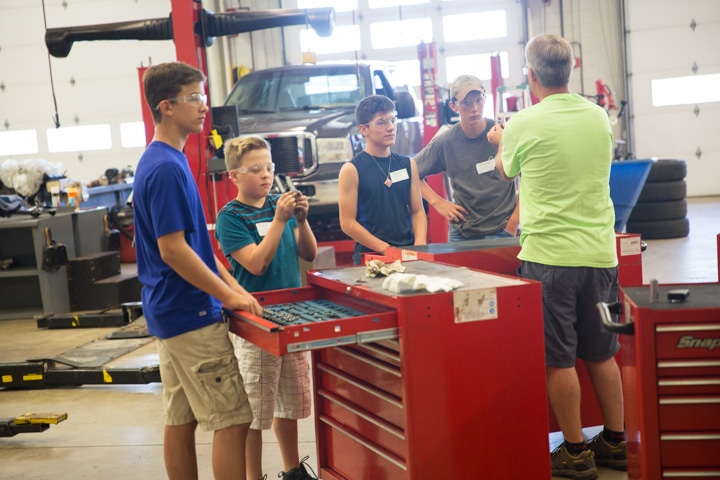 Students gather around tool boxes in automotive lab at Moraine Park Tech Knowledge College