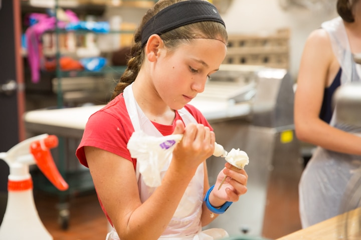Girl works on icing technique during culinary activity at Moraine Park TKC summer camp