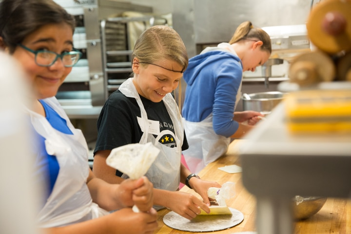 Girl smiles in kitchen during Moraine Park culinary activity at Tech Knowledge College