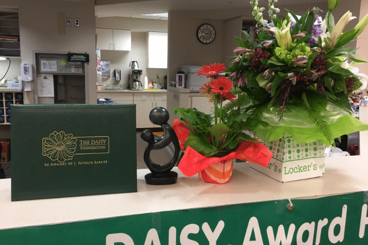 daisy award and flowers on counter