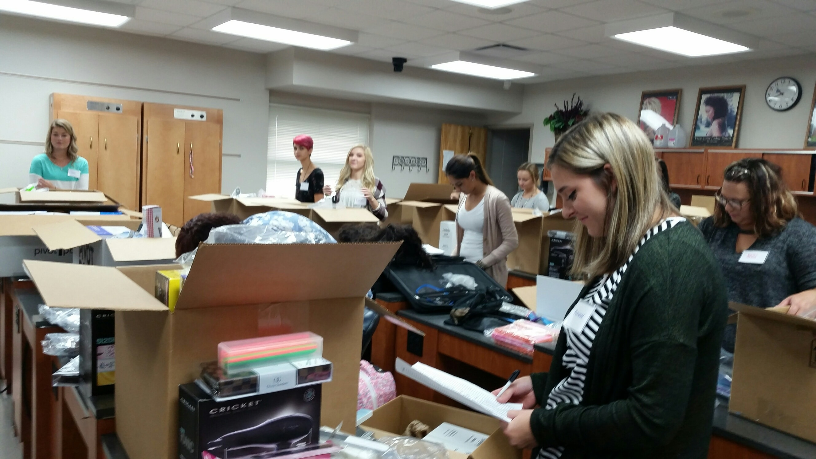 Moraine Park Cosmetology students opening cosmetology kits containing shears, razors, curling irons, combs, brushes, capes, makeup brushes, nails supplies, perm rods, color accessories and mannequin heads.