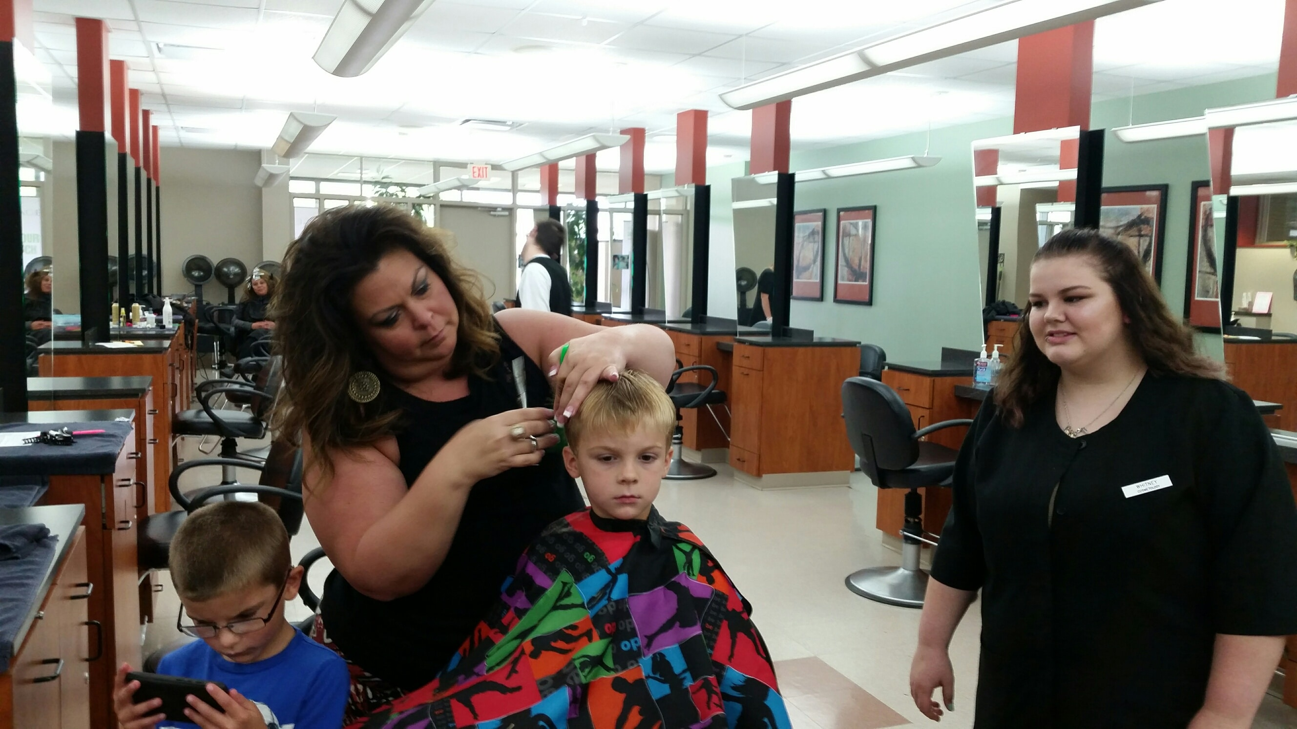 young boy getting haircut in moraine park salon by female stylist