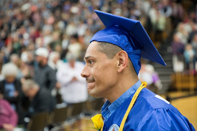 Moraine Park male graduate smiles with cap on