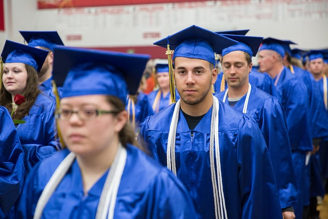 Male student walking with graduation cap and gown
