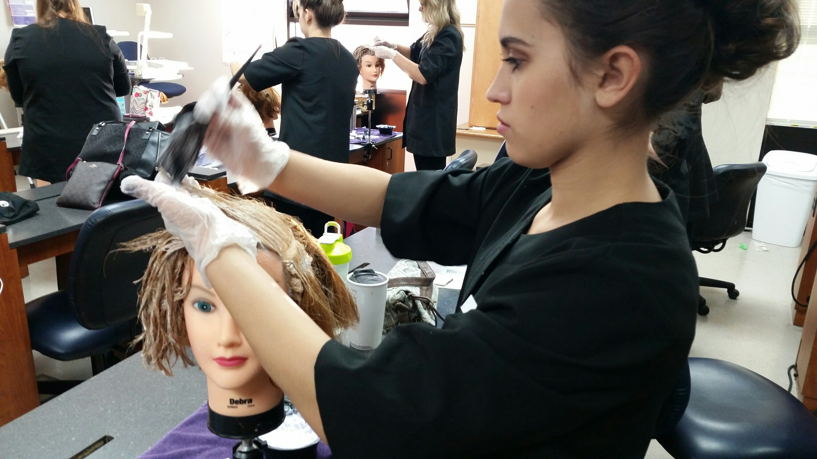 MPTC Cosmo student applying bleach on manikin