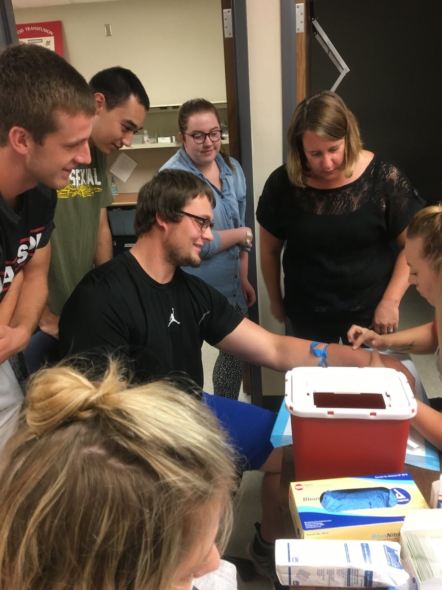 instructor watches students practicing drawing blood from man's arm