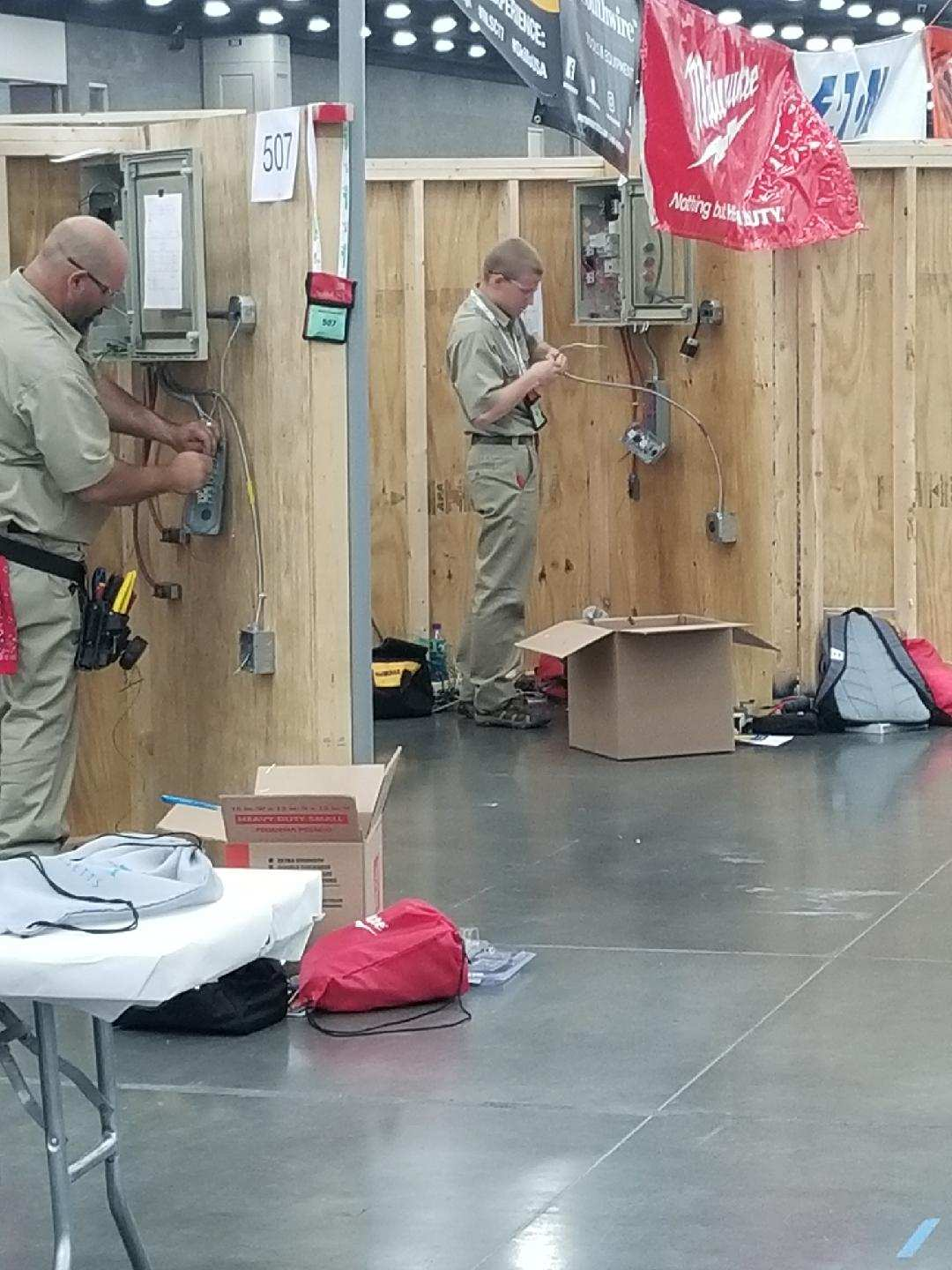 Students in competition by wooden walls at National Skills USA