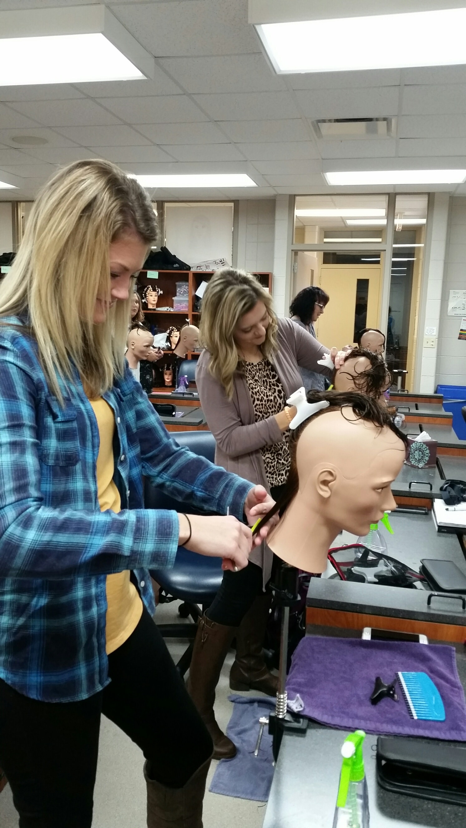 female student giving mannequin a haircut
