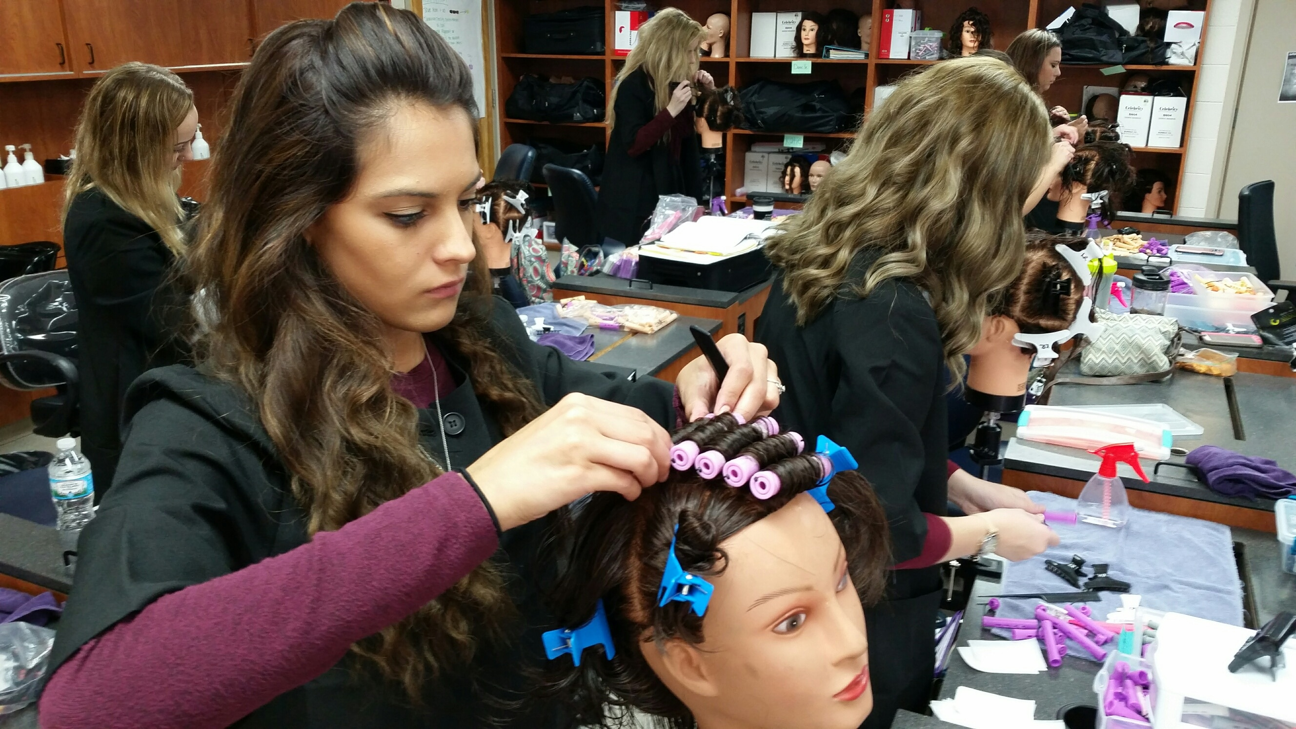 Moraine Park Cosmetology student practicing wrapping perm rods on manikin head