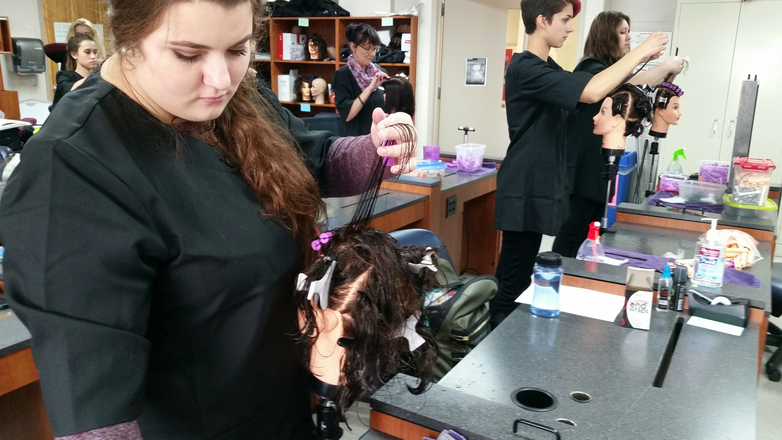 students working with mannequins to practice perms