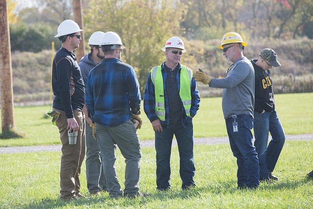 instructors, parents and students talk with hard hats on