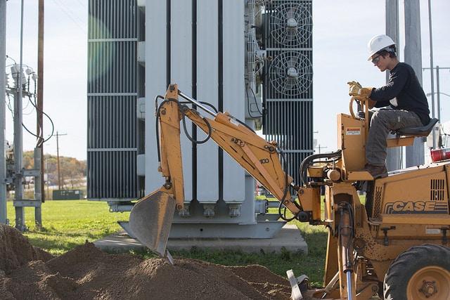man operates digging machinery