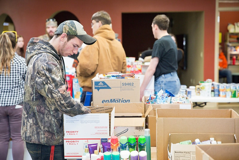 students fill boxes of donations for military members in beaver dam cafeteria