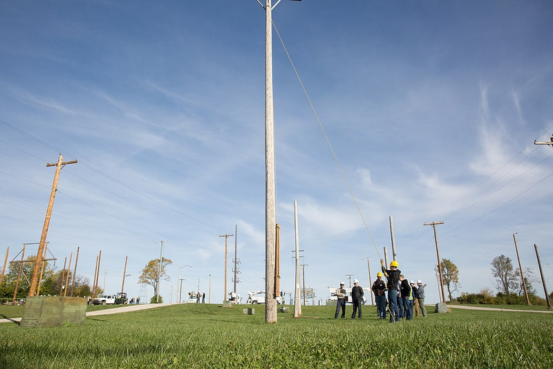 students stand near power poles and pull rope