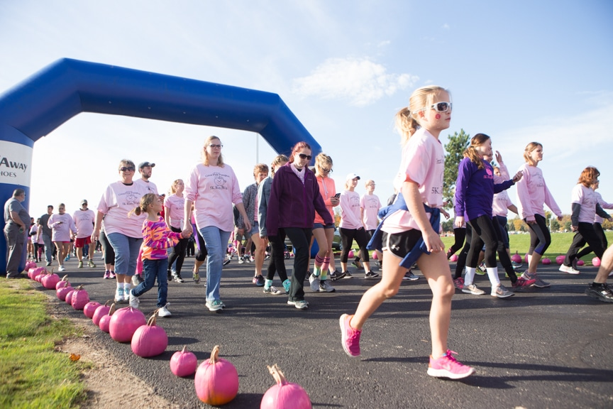 people of all ages run next to pink pumpkins