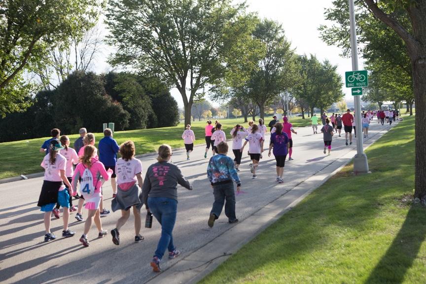 view of runners going down street at pink pumpkin