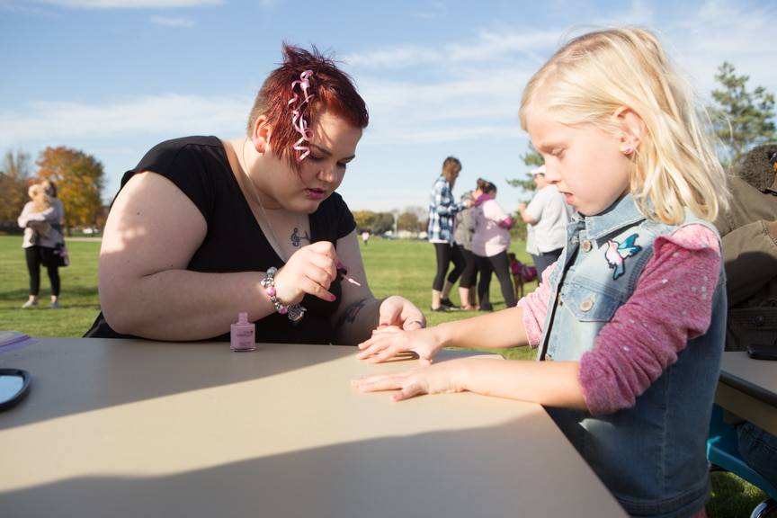 young girl gets nails painted at pink pumpkin