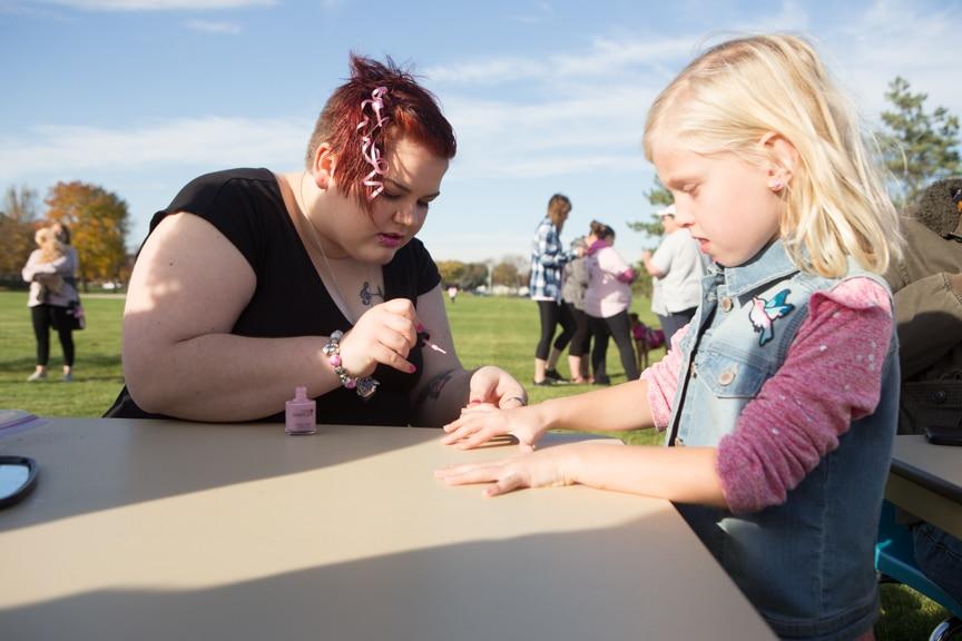 young girl gets nails painted at pink pumpkin