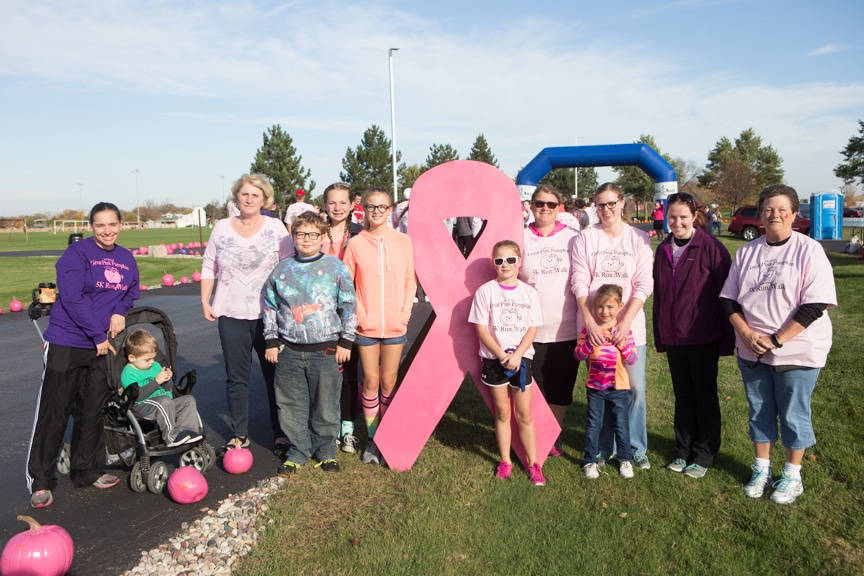 group poses next to breast cancer ribbon sign