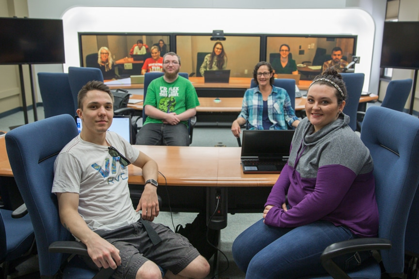 students gather in telepresence room