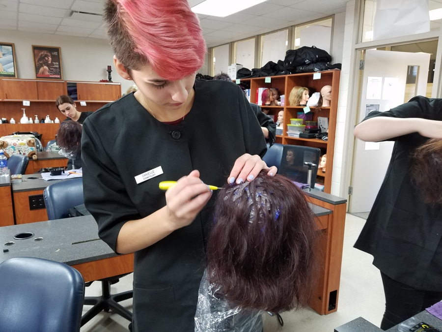 MPTC Cosmo students mixing hair lightener to put on manikin