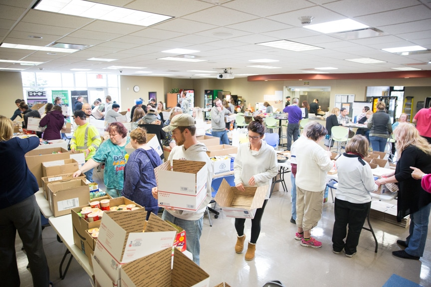 large group of people help pack boxes in moraine park beaver dam cafeteria