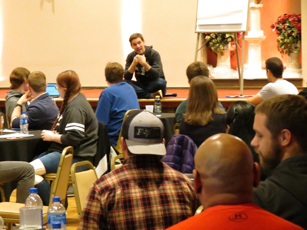 Keynote speaker, Ryan Penneau, addressing a large group of confernce attendees while sitting on the floor of the stage.