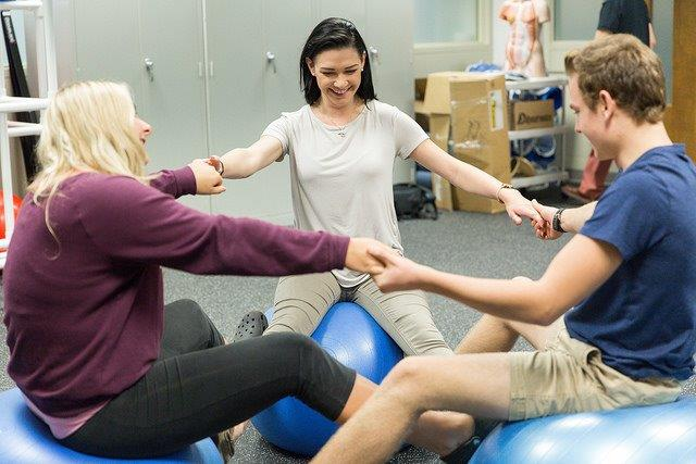 Three Health and Wellness students performing an activity on an exercise ball.