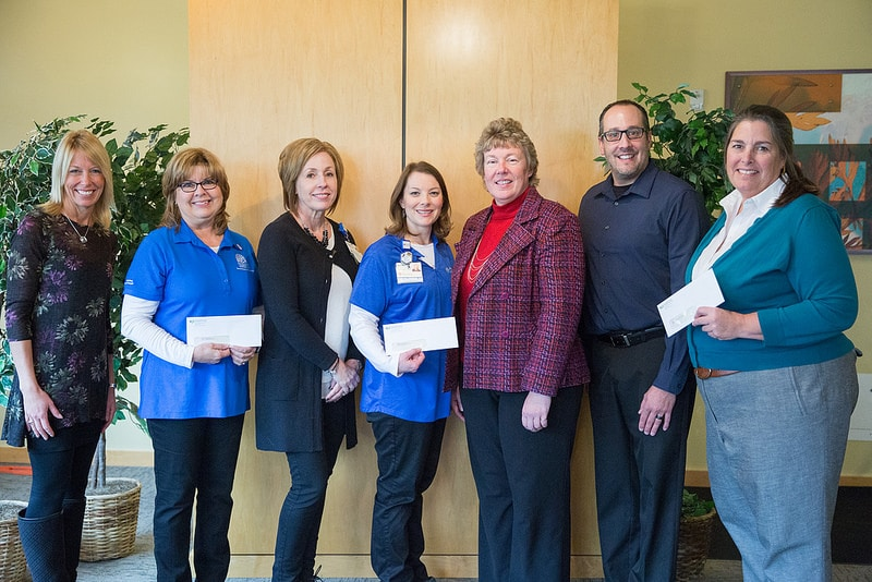 Area cancer group representatives hold up checks donated by moraine park technical college