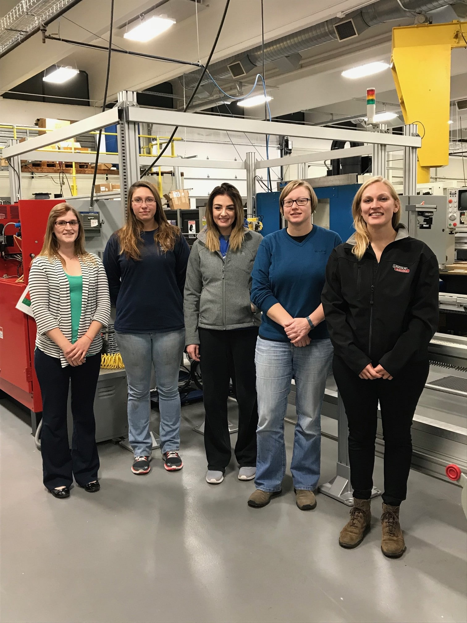 group of women stand in manufacturing area