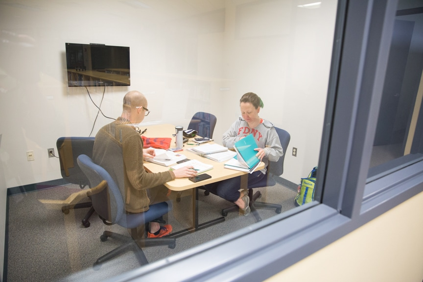 a male and a female student studying at a table in a library study room
